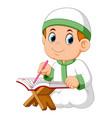 boy is sitting and reading al quran