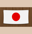 japan flag on a dark wood wall background vector image vector image