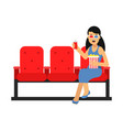 young woman sitting in the cinema with popcorn and vector image vector image