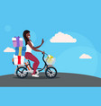 woman cycling bicycle carrying wrapped presents vector image