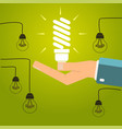 hand holding a bright energy saving light bulb vector image