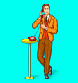 pop art man talking on a retro phone and shows vector image vector image