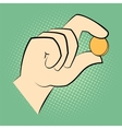 hand holding a coin between two fingers vector image