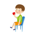 Flat boy sitting at chair eating apple
