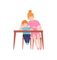 mom and son sitting at desk young woman teaching vector image vector image