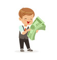 happy little boy businessman holding a stack of vector image