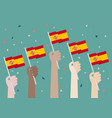 hands holding up spain flags vector image