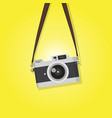 hanging vintage camera over yellow background vector image vector image