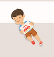 cute little boy lying on his back and holding vector image