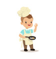 cute little boy chef frying egg in a flying pan vector image vector image