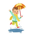 cute little boy holding colorful umbrella playing vector image vector image