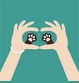two womans hands holding cute cat dog paw print vector image vector image